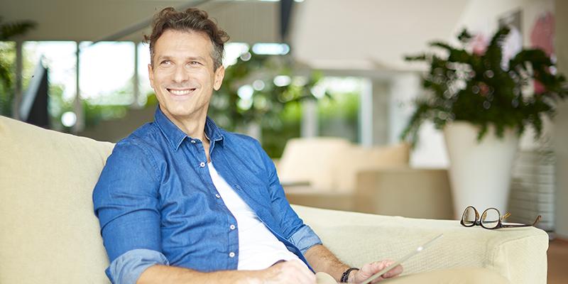 Un uomo seduto su un divano mentre legge il tablet